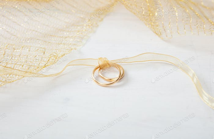 Two golden wedding rings tied with a golden ribbon on white wooden background
