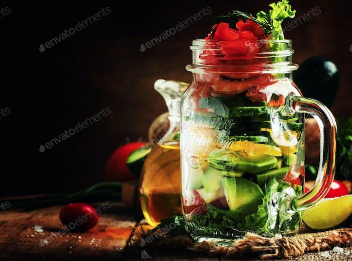 Gesundes Essen: Salat mit Gemüse, Salat, Lachs und Garnelen in einem Glas