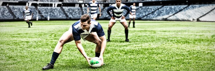 Digital composite image of rugby player picking up the ball in sports stadium