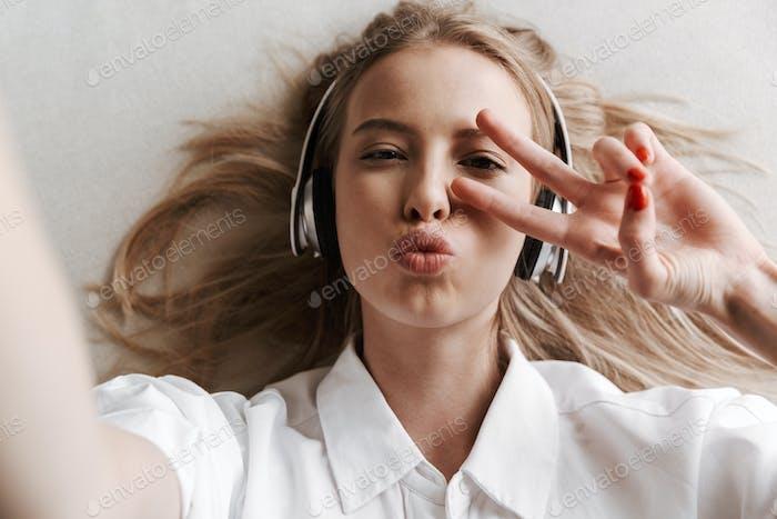 Draufsicht der fröhlichen jungen Frau in Kopfhörern
