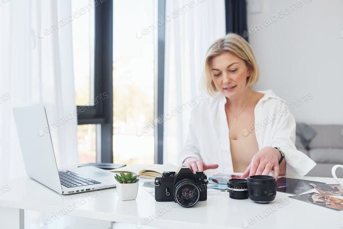 Middle-aged woman in elegant clothes is at home. Photographer with camera