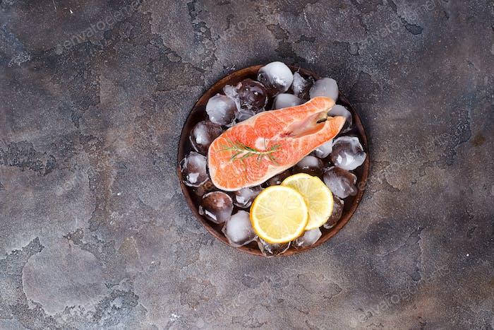 Lachssteaks auf Eis mit Zitronenscheibe auf Holzteller. Magere Proteine.