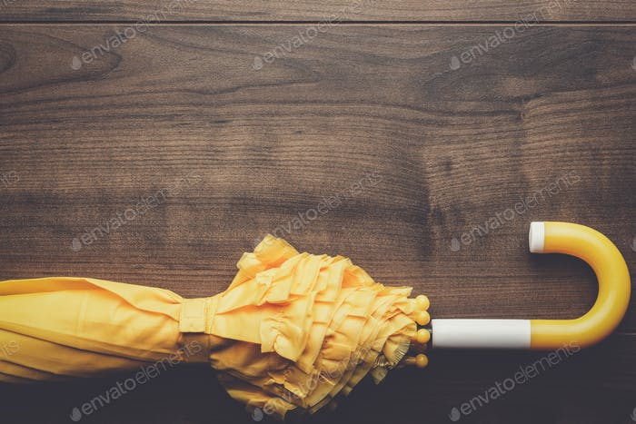 folded yellow umbrella on the table