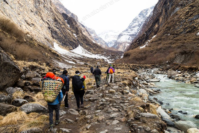 Group of people trekking on a valley towards the Annapurna mountain summit in Nepal