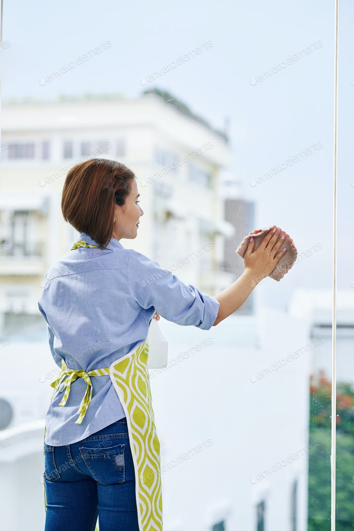 WOman cleaning big window