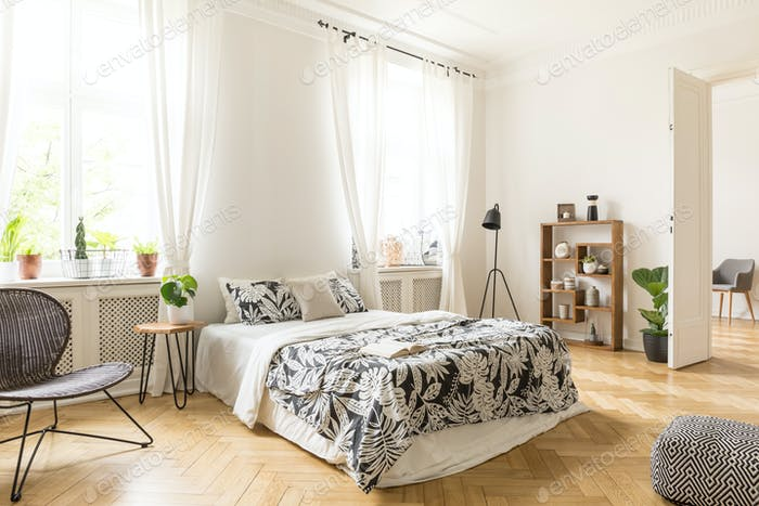 An interior of a bedroom with herringbone parquet, white walls a