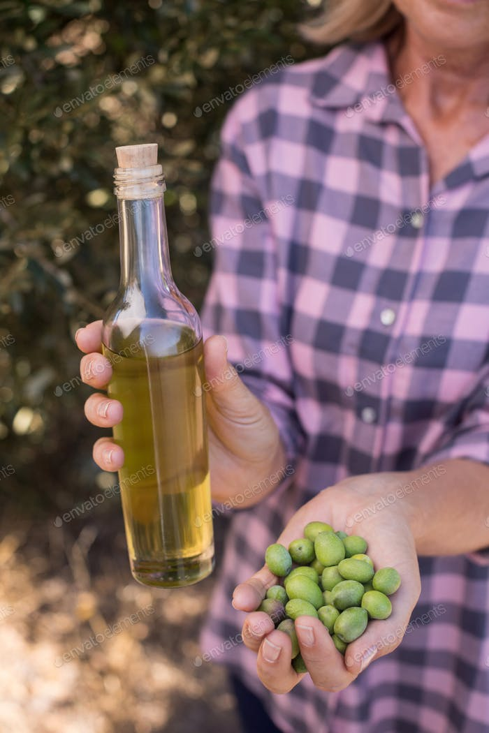 Woman holding olive oil and harvested olives