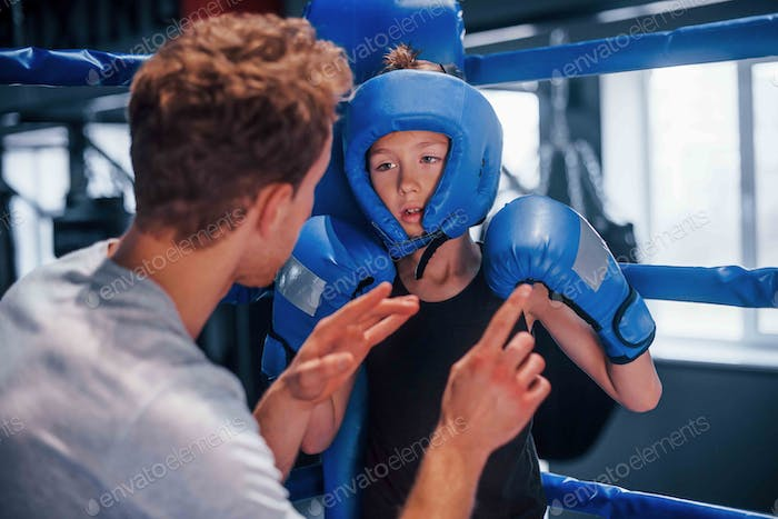 Young boxing coach is helping little boy in protective wear on the ring between the rounds