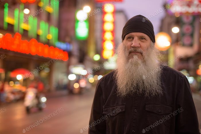 Mature tourist man with long beard thinking in Chinatown at night