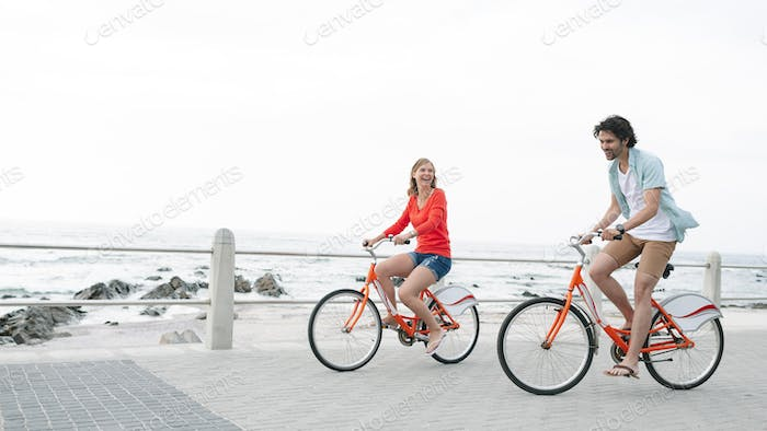 Couple riding bicycle on pavement near promenade at beach