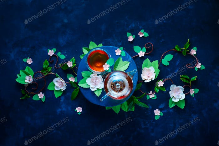 Blooming apple tree branch with teapot and double wall glass tea cups. Dark blue background flat lay
