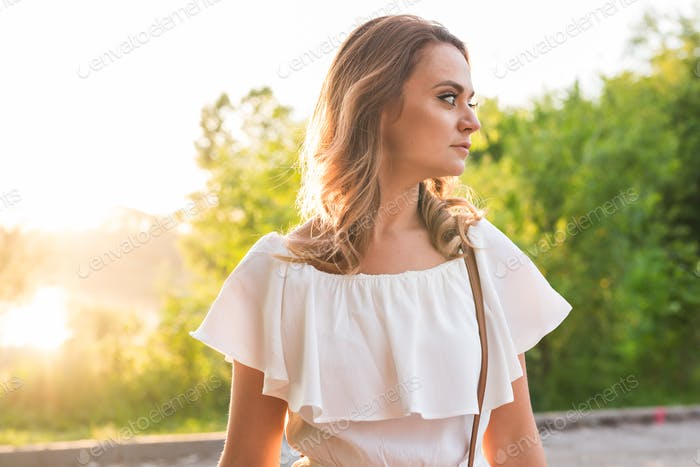 Attractive young woman enjoying her time outside in park with sunset in background