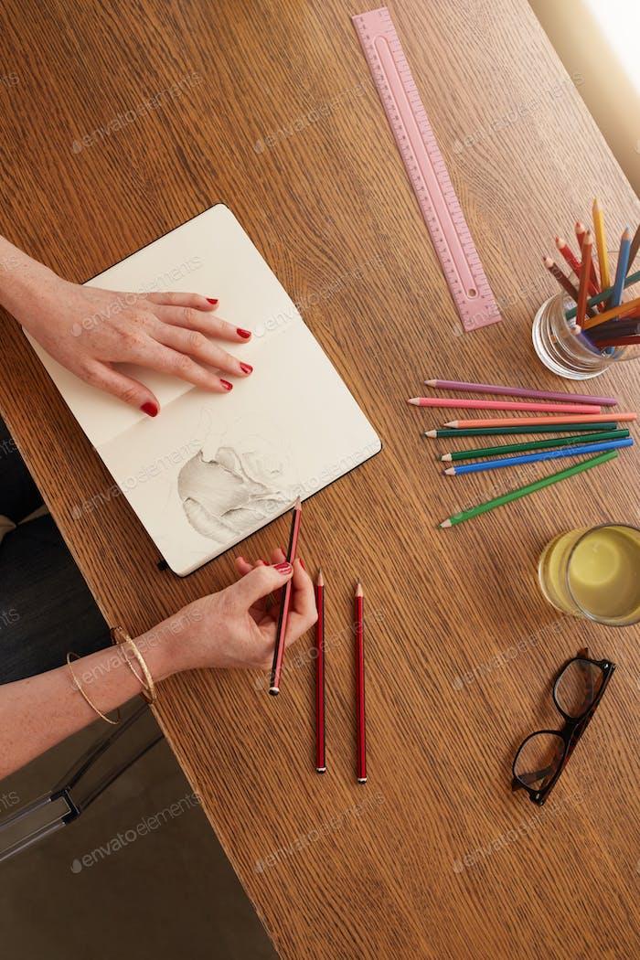 Frau Hände machen eine Blume Skizze auf Skizzenbuch