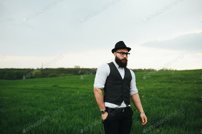 A man with a beard and sunglasses walking on the field