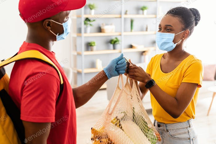 Courier Delivering Bag With Grocery Products To Lady At Home