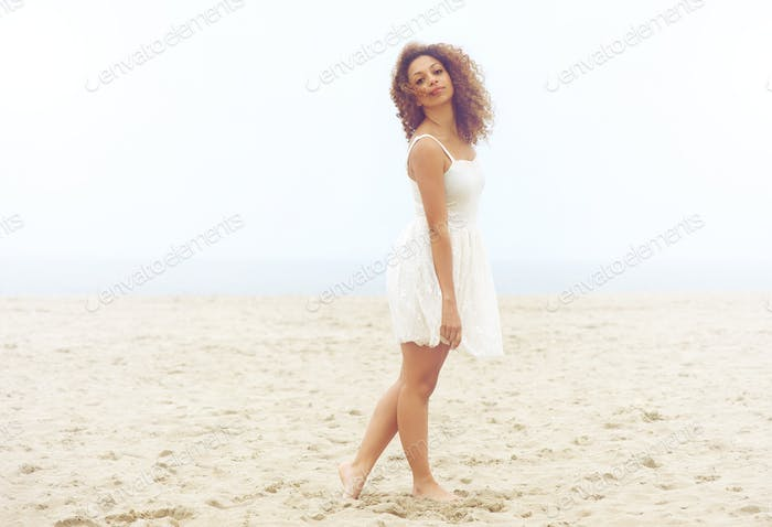 Beautiful woman in white dress walking on sand at the beach