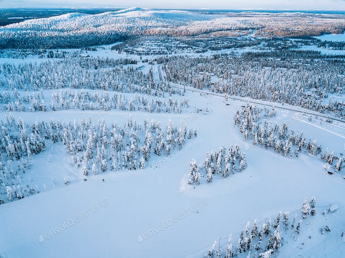 Aerial view of snow winter landscape with mountains, snow covered forests