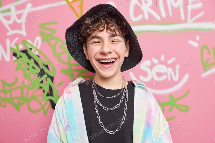 Happy teenage biy with braces on teeth wears stylish clothes with chains around neck has fun with fr