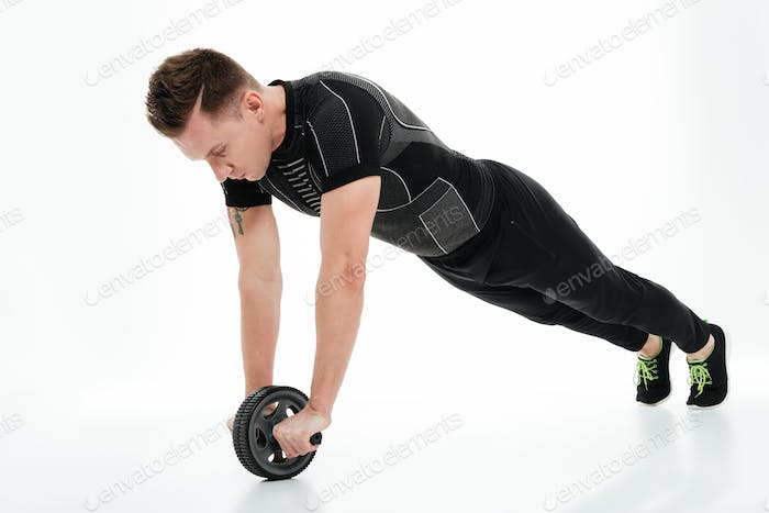 Full length portrait of a concentrated healthy sportsman doing exercises