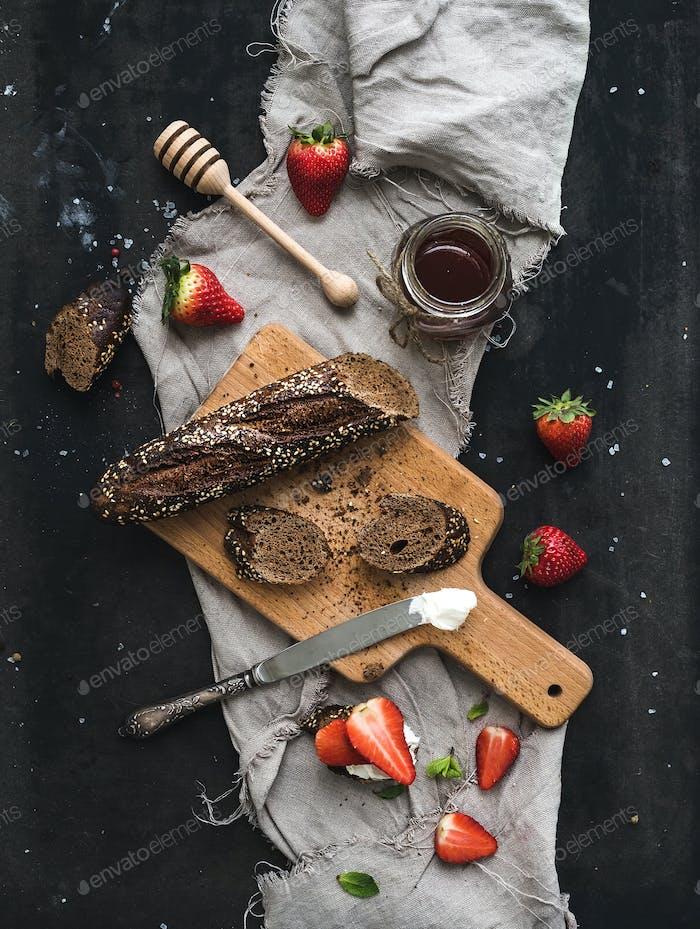 Frühstücksset Schwarzer Baguette-Toast mit frischen Erdbeeren, Honig und Mascarpone-Käse