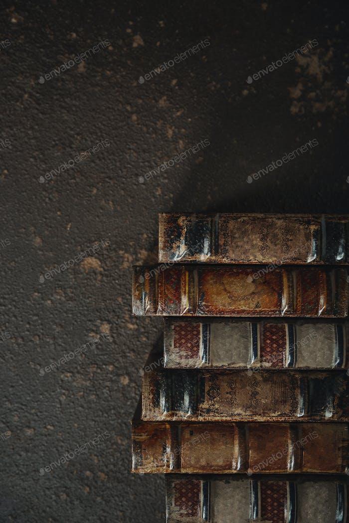 Lazo plano antiguo con pila de libros encuadernados de cuero antiguo sobre un fondo oscuro