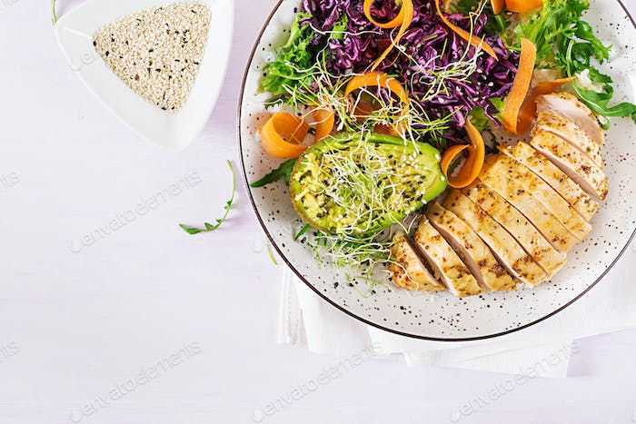 Buddha bowl dish with chicken fillet, avocado, red cabbage, carrot, fresh lettuce salad and sesame.