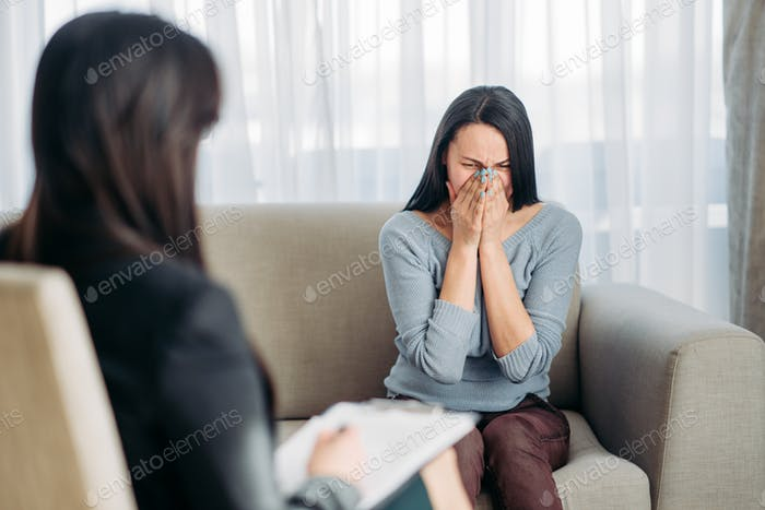 Female patient sitting on sofa at psychotherapist