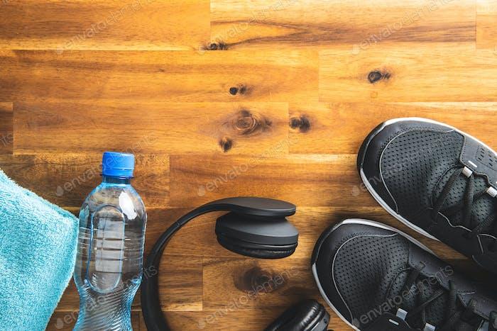 Fitnesskonzept Schwarze Sportschuhe, Kopfhörer, Hantel und Flasche Wasser