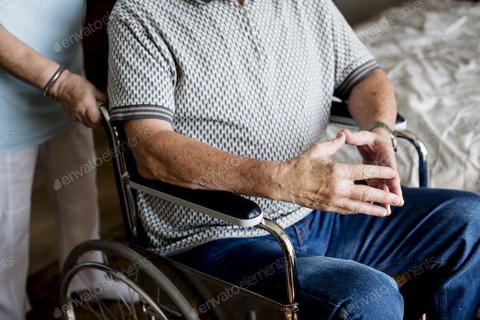 Seniorenpaar, Frau schiebt einen Rollstuhl ihres Mannes