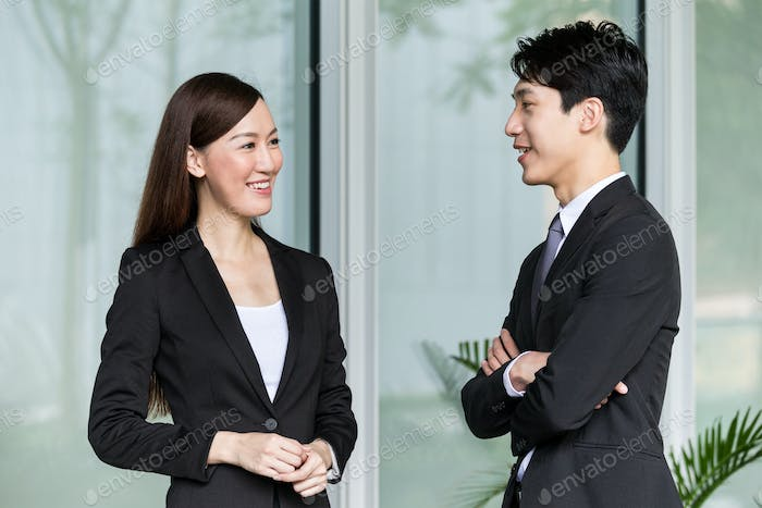 Businesswoman and businessman discuss together