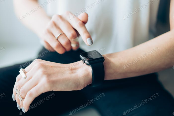 Woman's hand touching the screen of a smart watch
