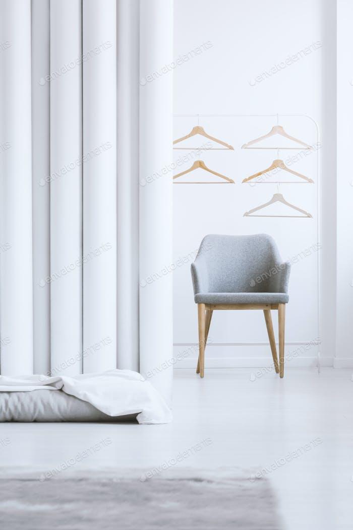 Wooden hangers above gray armchair