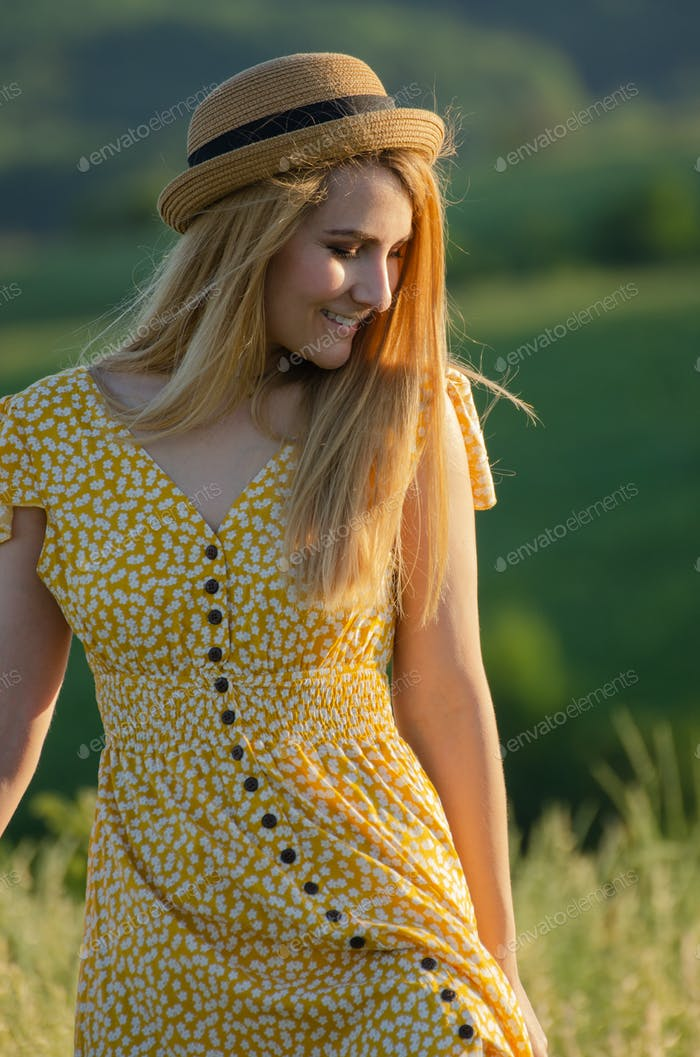 Young blond caucasian female model enjoying outdoor activity at meadow summer evening time
