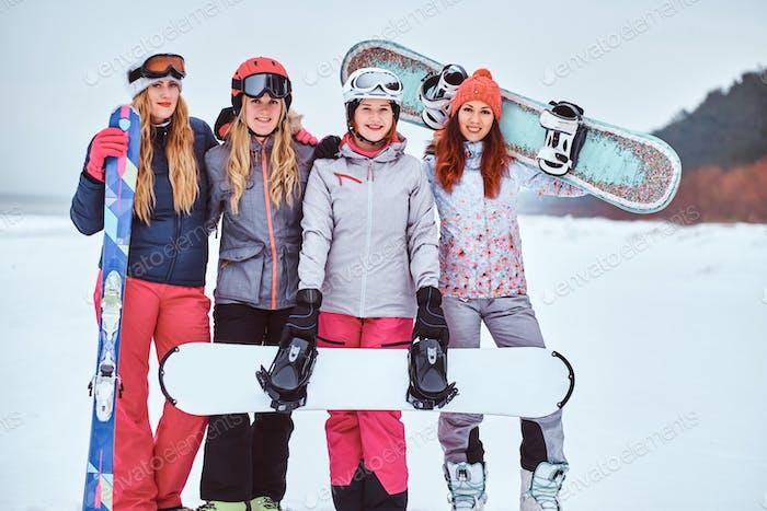 Las mujeres amigas en ropa deportiva de invierno con tablas de snowboard y esquís de pie juntos en una playa nevada