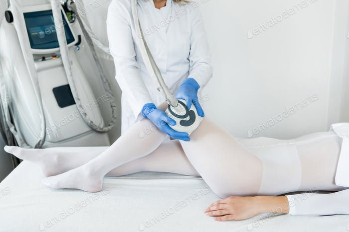 woman having procedure of lipomassage in apparatus cosmetology clinic