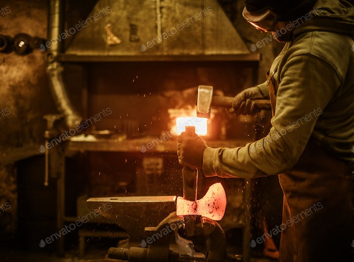 The blacksmith forging the molten metal on the rusty vise in smithy