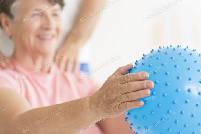 Elderly woman holding blue ball