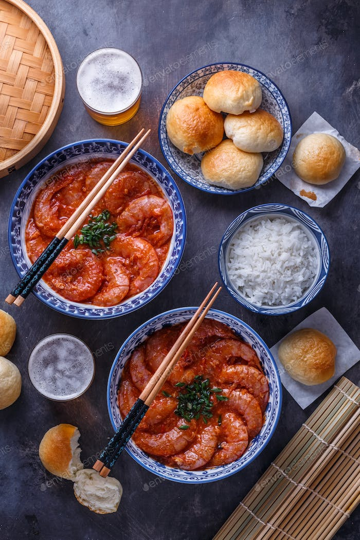 Spicy asian shrimps in tomato sauce with rice, buns and beer, top view