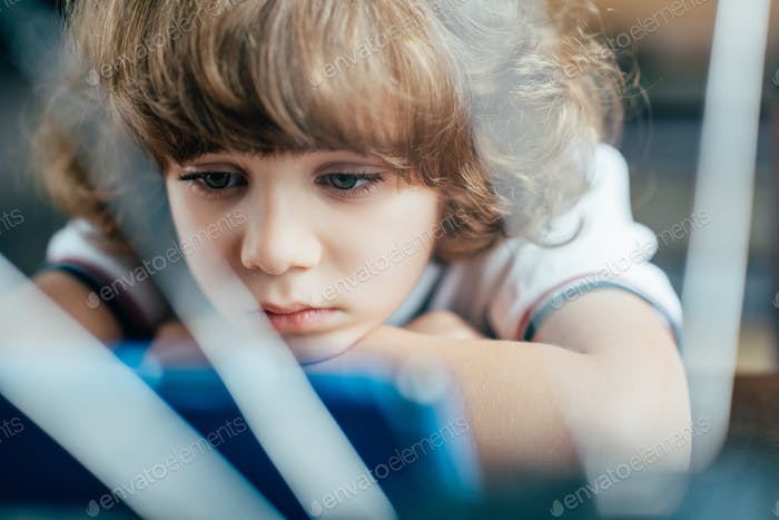 thoughtful curly kid looking at digital tablet