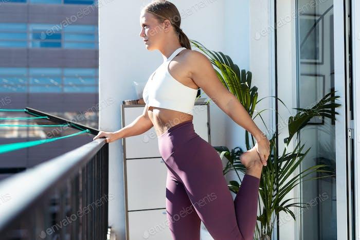 Schöne gesunde junge Frau macht zu Hause Dehnübungen auf dem Balkon.