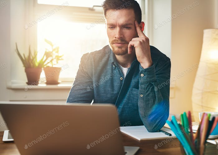 Frowning businessman reading data on his laptop