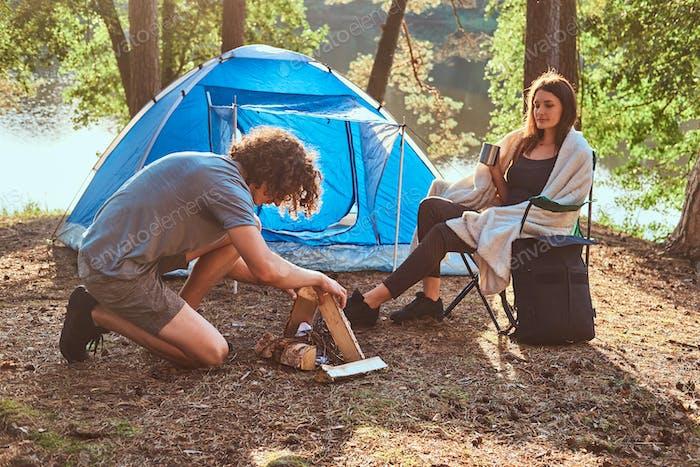 Paar junge Reisende verbringen Tag im sonnigen Wald in der Nähe von Zelt