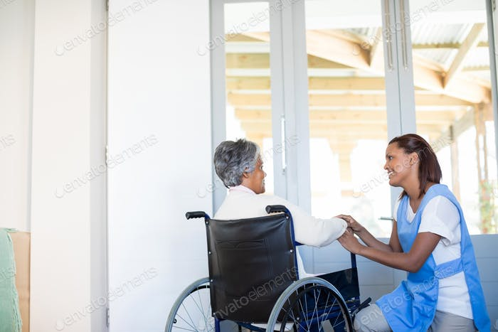Female doctor interacting with senior woman on wheelchair