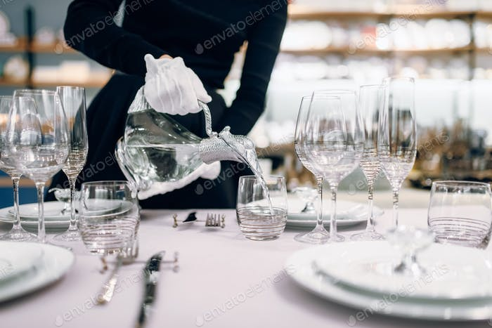 Waitress pours drinks into glasses, table setting