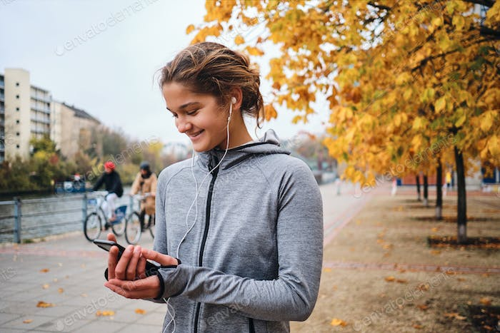 Portrait of cheerful sporty girl in earphones happily using cellphone preparing running in park
