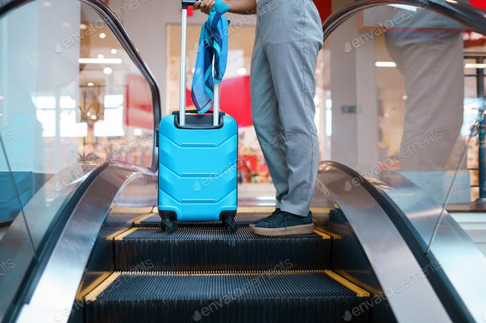 Young woman with suitcase on escalator in airport
