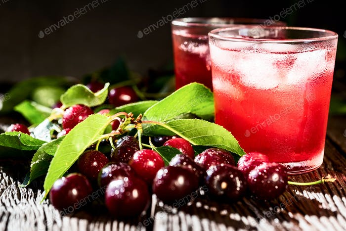 Fresh cherries and ice cherry fruit drink on wood