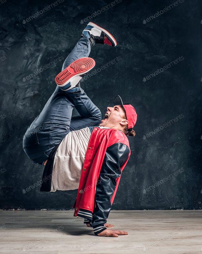 Emotional stylish dressed man performing break dance moves on the floor.