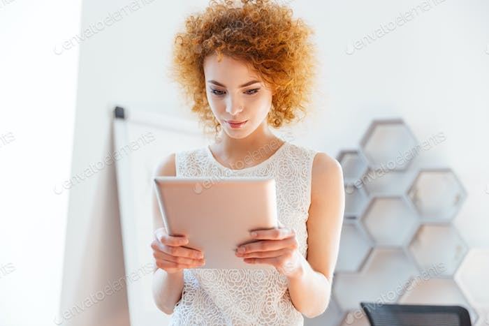 Serious business woman using tablet in office