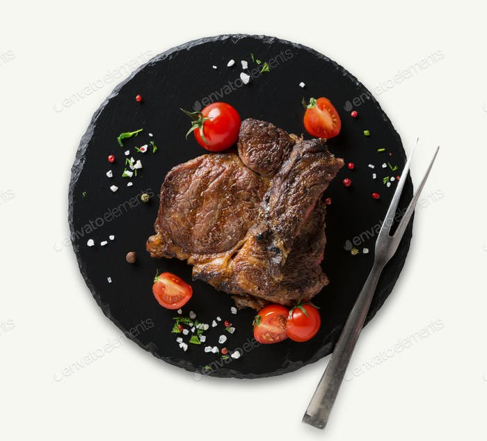 Rib eye steak on black plate, closeup, isolated
